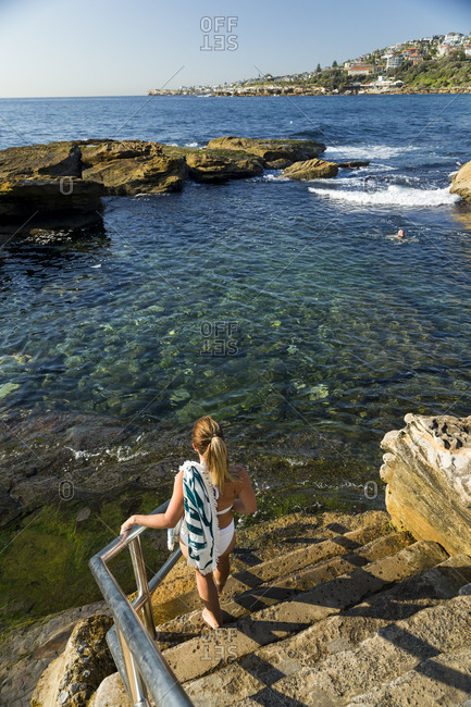 Young woman walking down stairs to sheltered swimming area at Coogee Beach in Sydney, Australia