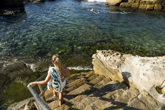 Young woman descending stairs to swimming area at Coogee Beach in Sydney, Australia