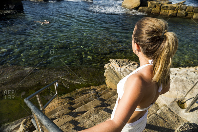 Young woman on stairs leading to sheltered swimming area at Coogee Beach in Sydney, Australia
