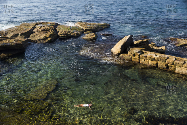 Sydney, Australia - February 24, 2017: Scenic view of woman swimming in sheltered bay at Coogee Beach