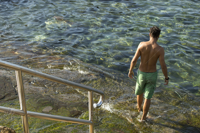 Young man going into sheltered swimming area at the base of stairs at Coogee Beach in Sydney, Australia