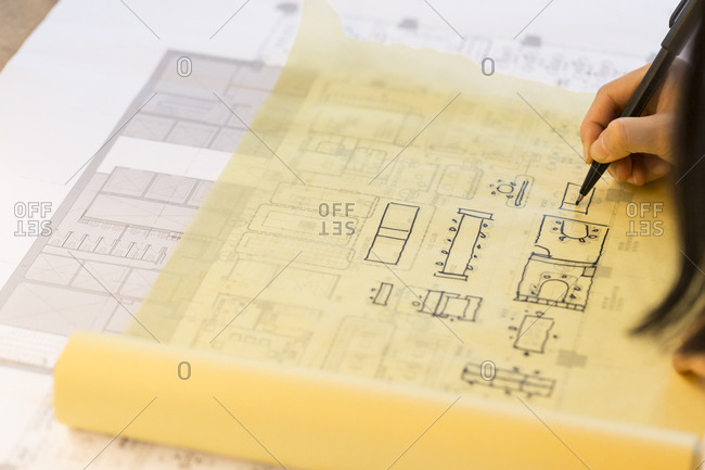 Person tracing an architectural plan