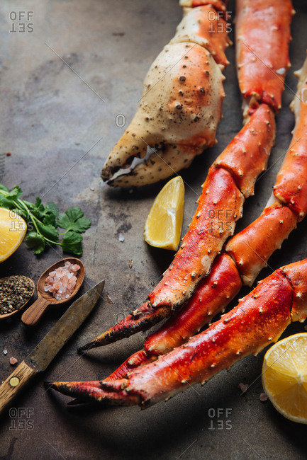 Crab legs and claw with seasonings and lemon on black background