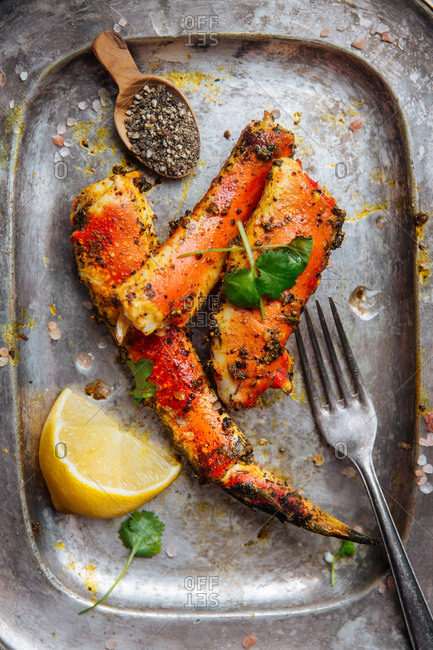 Silver platter of crab legs with lemon and seasonings