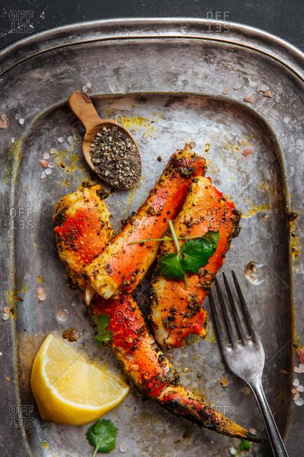 Silver platter of seasoned crab legs with lemon