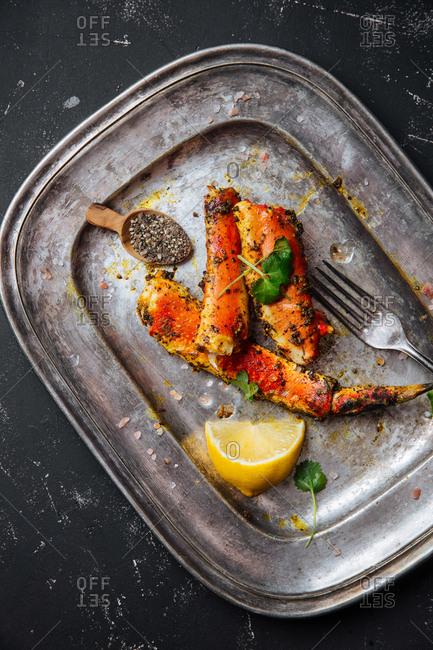 Seasoned crab legs on silver platter with lemon