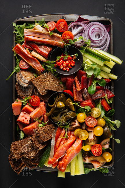 Colorful platter of smoked fish with vegetables and bread