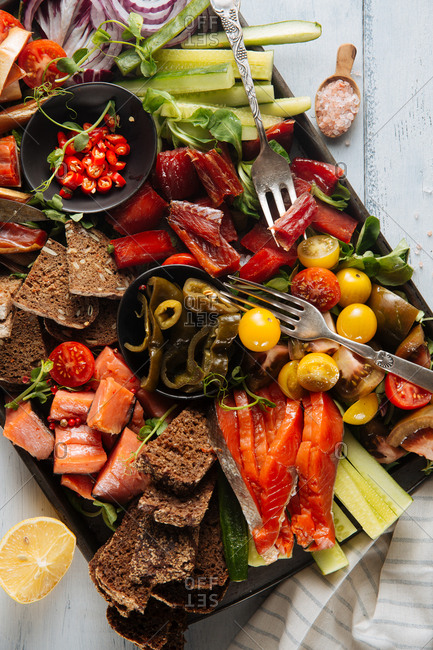 Arrangement of smoked fish and vegetables on platter