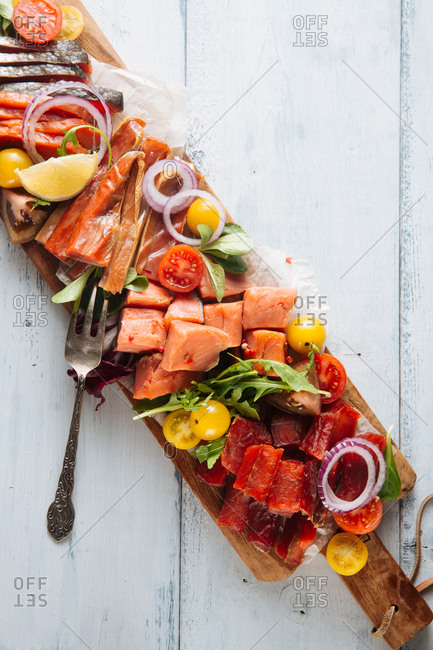 Smoked fish on a long wooden board with vegetable garnish