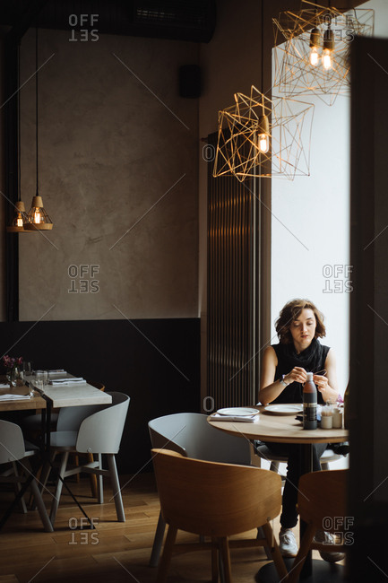 Woman seated at window table in restaurant
