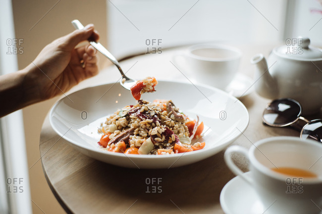 Woman eating grain bowl with tomatoes and vegetables at restaurant