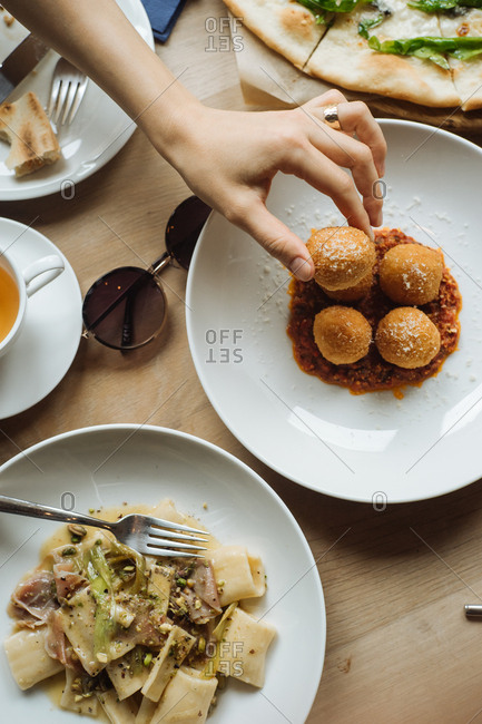 Woman's hand with dish of fritters and pasta