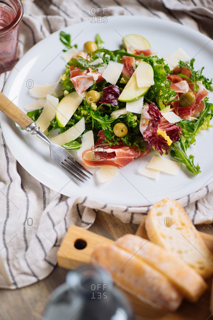 Salad with cured ham, olives and apples served with bread