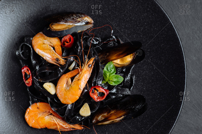 Prawns and mussels served on black pasta