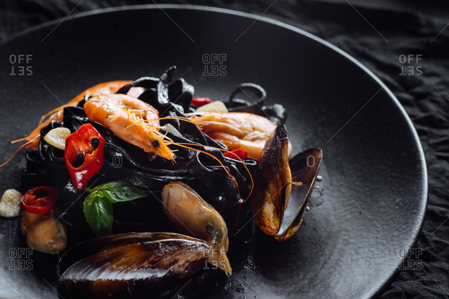 Fresh mussels and prawns on black pasta