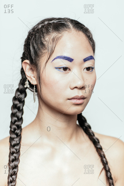 Portrait of an Asian woman with braids and blue makeup