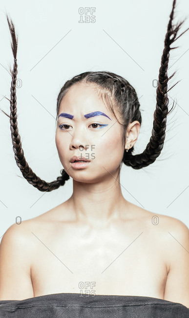 Portrait of an Asian woman wearing blue makeup with her braids sticking up in the air