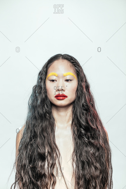 Portrait of an Asian woman with long hair and yellow eyebrows