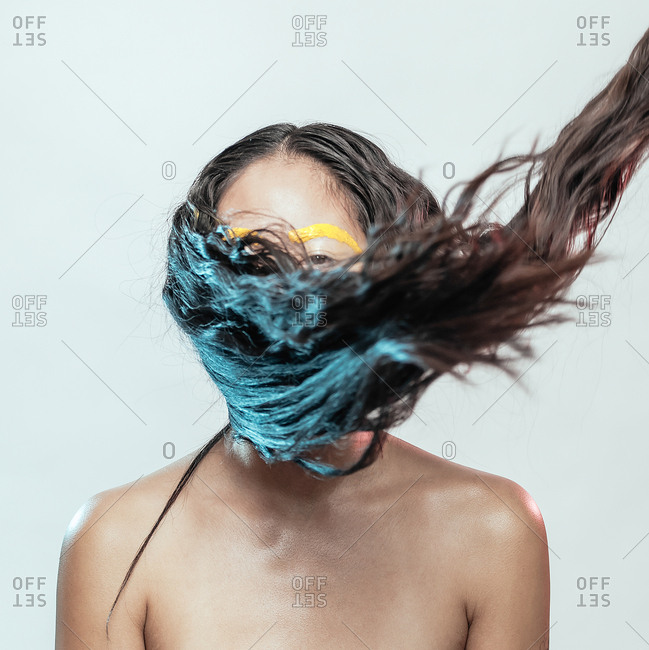 Portrait of a woman with crazy makeup and hair covering her face