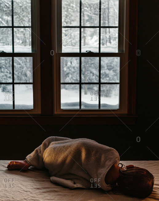 Child in towel lying on bed watching snow fall out window