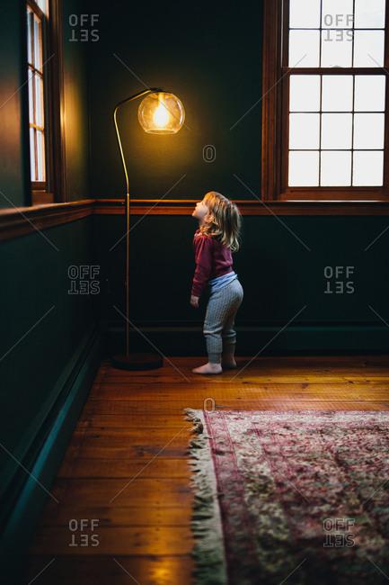 Toddler girl looking up at lamp