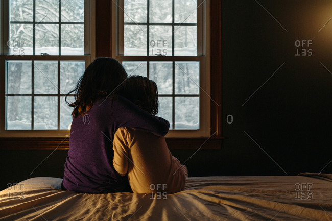 Two young siblings sitting on bed watching snow fall out window