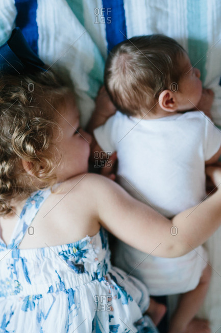 Toddler girl holding her infant brother on bed