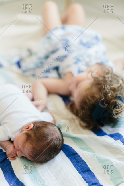 Newborn baby and sister lying together on bed