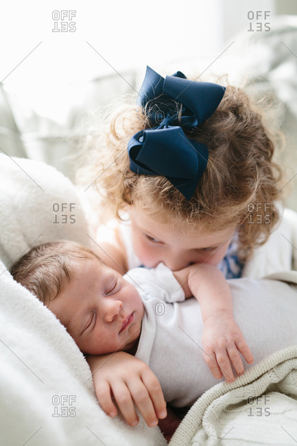 Affectionate toddler girl gazes at her newborn sibling