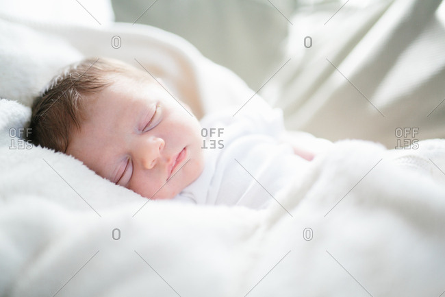 Adorable newborn baby asleep in sunlight