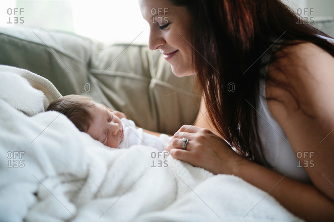 Woman gazing at her sleeping infant son