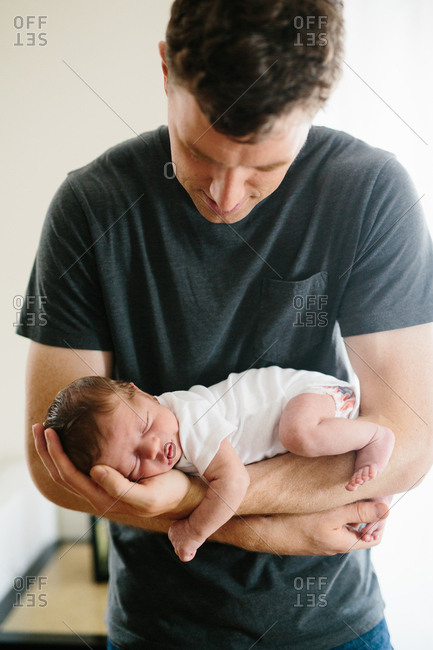 Man cradling infant son in his arms