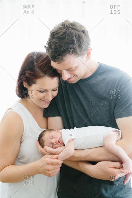 Parents gazing at their sleeping newborn son