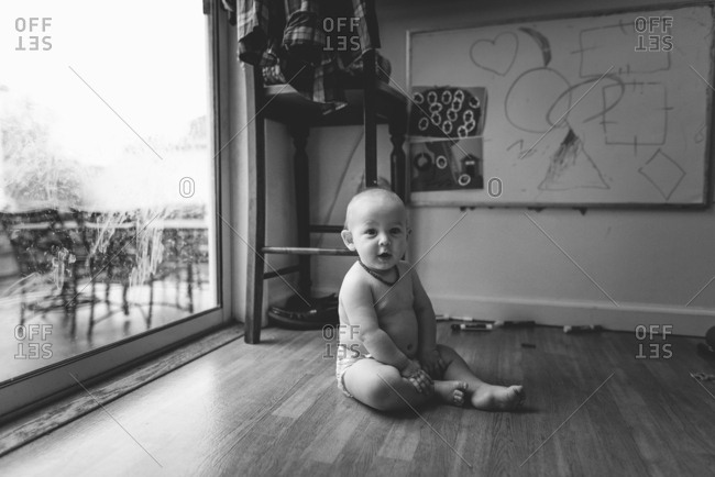 Chubby baby sitting on floor in black and white
