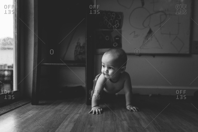 Baby crawling on floor in black and white