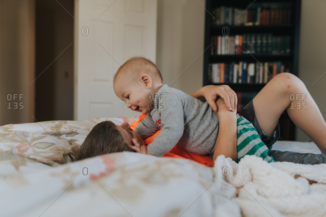 Boy playing with baby brother on a bed