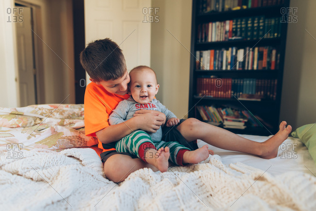 Boy holding baby brother on a bed