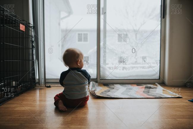 Baby sitting on floor looking out glass door