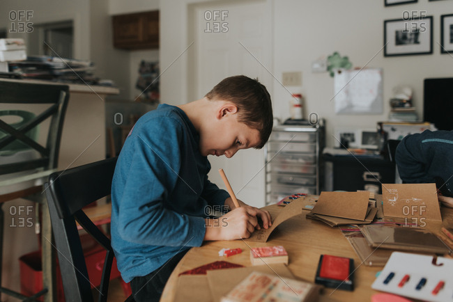 Boy writing in Valentine cards