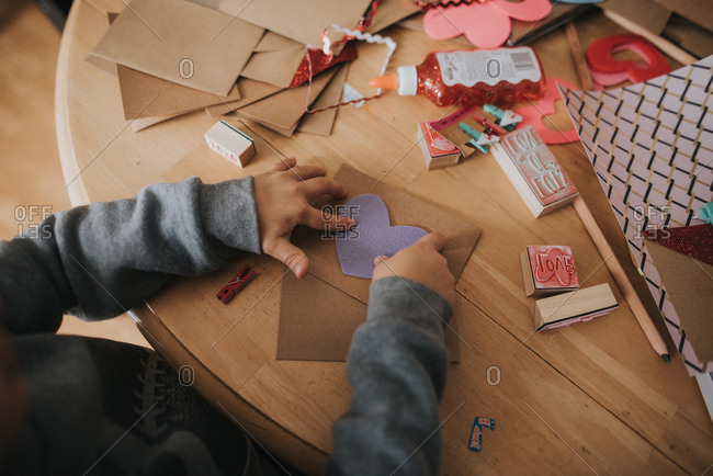 Boy putting hearts onto a Valentine\'s day card