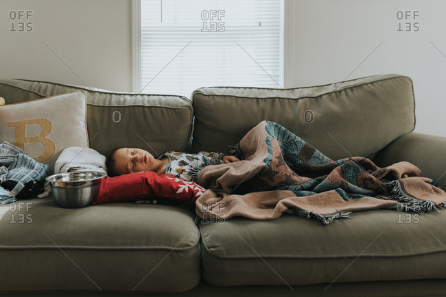 Boy lying on sofa with bowl while sick