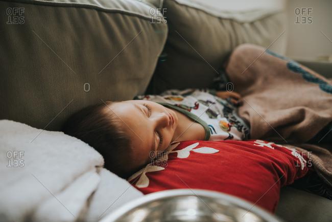 Sick boy lying on sofa
