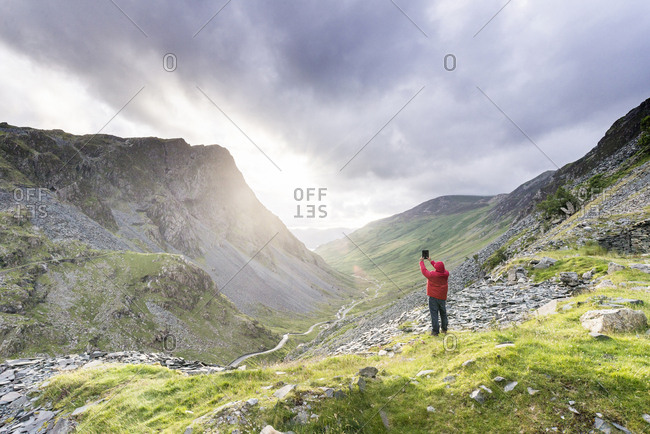 Man taking photo of landscape with digital tablet