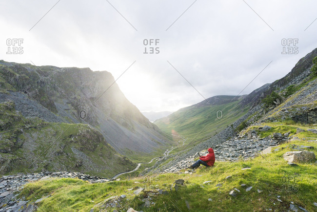 Man reading digital tablet in mountains