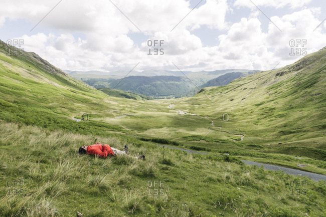 Man lying in grass in valley, England