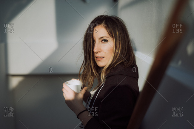 Young woman standing on stairs drinking cup of coffee