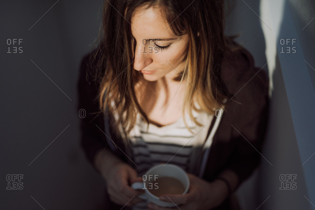 High angle view of woman drinking cup of coffee