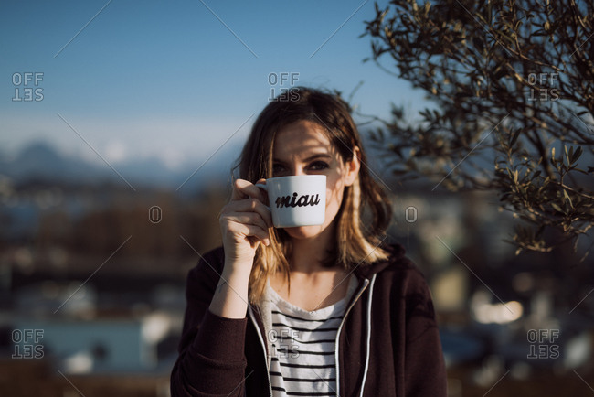 Young woman holding cup of coffee in front of her mouth