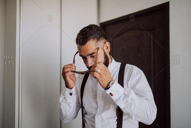 Groom putting on wooden sunglasses