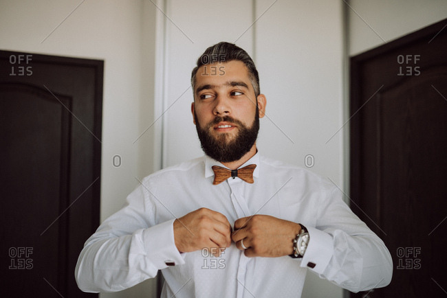 Groom buttoning his shirt